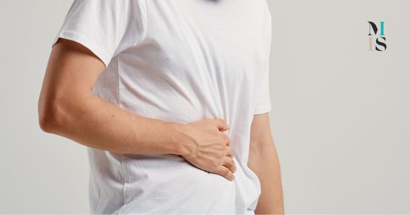 Man in white tee shirt holds lower abdomen to support abdominal hernia before undergoing hernia repair. MIIS logo at top right